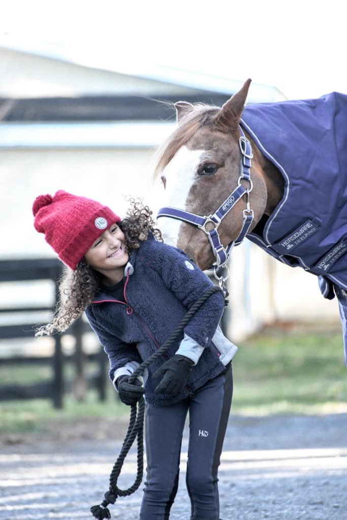 child smiling with pony