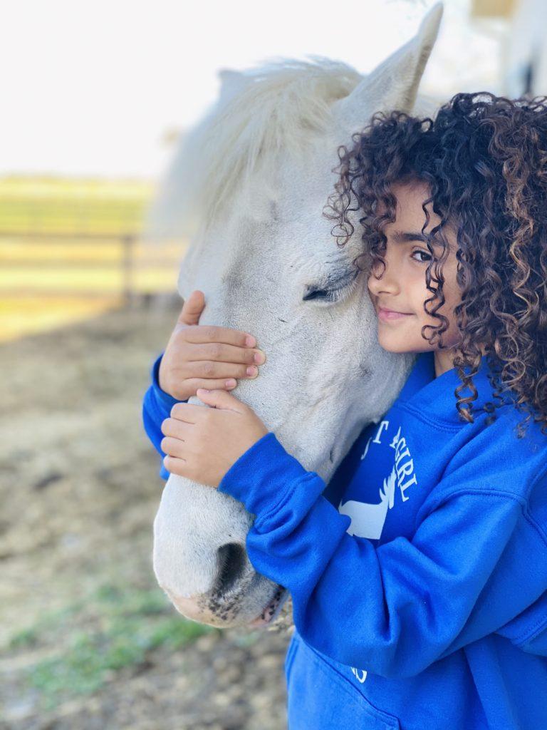 girl hugging pony