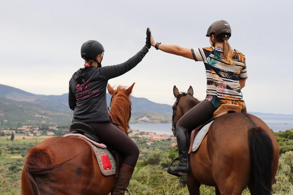 women on horseback high five
