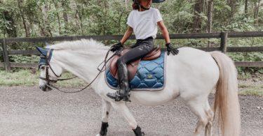 girl walking pony down road